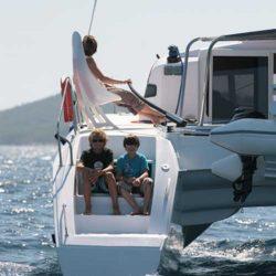 Zwei Kinder sitzen achtern auf Outremer-Catamaran