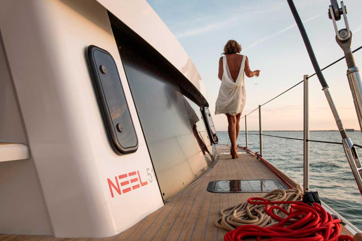 Junge Dame geht auf Deck vom Trimaran NEEL 51